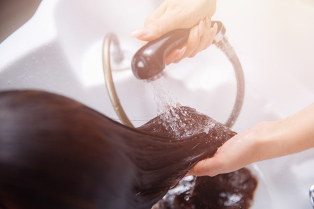 Master hairdresser woman shampooing in white sink spa salon hair. Stock Photo