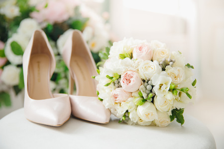 Wedding accessories bride bouquet of white peonies and shoes