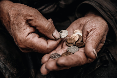 Concept Pension of Russia. Dirty hands old man poor with coin ruble.