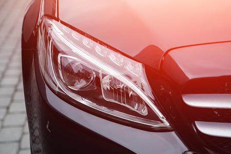 Closeup headlight luxury sedan car lighting road.