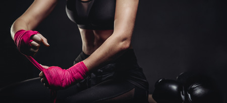 Women self defense. Girl pulls bandage on his fist and wears boxing glove. Dark background