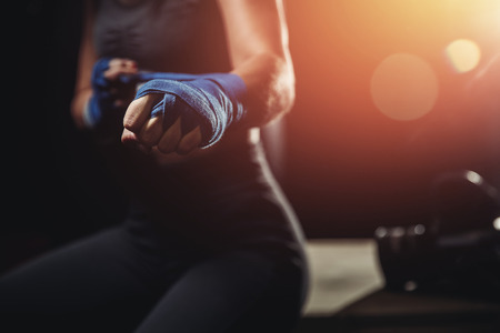 Woman wraps her fists in blue bandages for boxing gloves. Dark background. Concept femenism defense Stock Photo