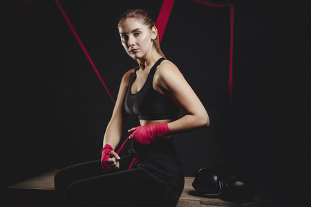 Athletic boxer girl wraps bandages on her hands puts gloves for fight in gym