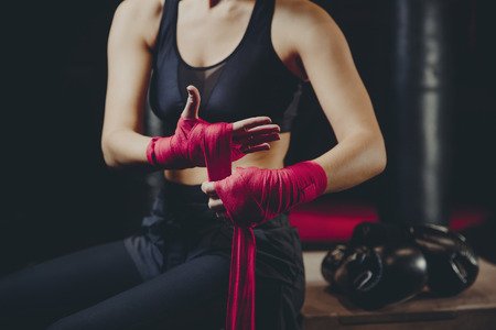 Athletic boxer female wraps bandages on her hands puts gloves for fight in gym