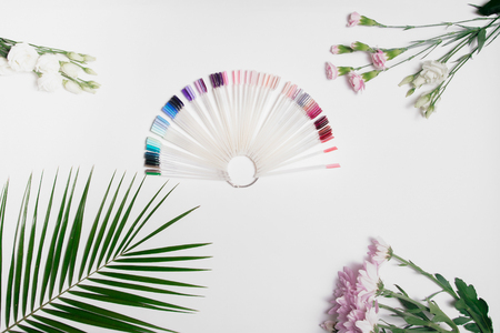 Fan from palette colors of gel varnishes for manicure are on table in center composition, next to palm green leaf and light pink flowers. Top view