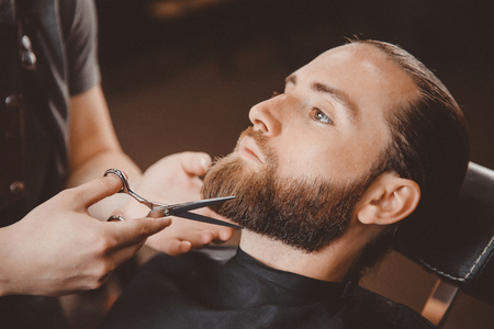 Hipster client man visiting in barber shop shaving beard scissors