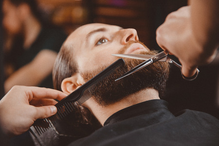 Barber shop shaving. Man hipster in chair, hairdresser styling his hair