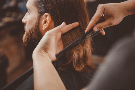 Process of cutting hair with scissors, hairdresser for men.