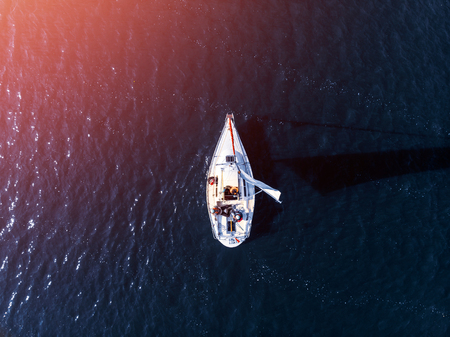 Aerial drone expensive yacht with white sail on blue water of sea. Concept travel