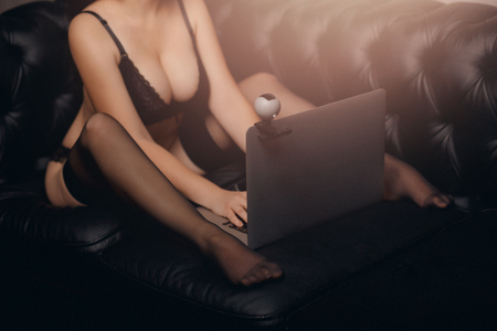 Internet webcam model beautiful young woman working in sex chat online. Stock Photo