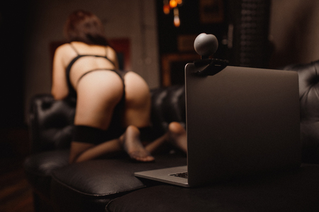 Seductive woman working on as Internet webcam model. Concept virtual sex chat.