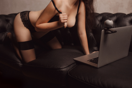 Woman working as Internet webcam model. Shows breasts. Concept virtual sex chat. Stock Photo