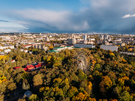 Sunny day. Blue October sky and huge Ferris wheel amusement Park, shrouded in autumn mood yellowed trees. Aerial drone. Minsk, Republic Belarus