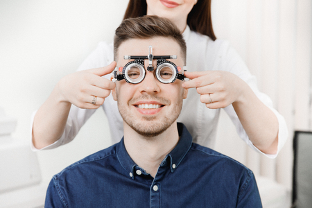 Man sits and smiles in an iron frame for selection of glasses lenses eyes. Concept reception ophthalmologist. Stock Photo