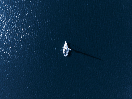 Alone white sail in sea blue on bright Sunny day casts shadow from bird eye view Stock Photo