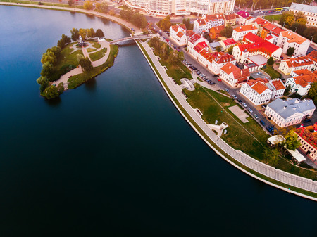 Small island, white chapel on it, in middle huge blue lake, through which passes bridge to city, houses with interesting architecture and crane roofs. Minsk, Republic of Belarus. Top view aerial drone