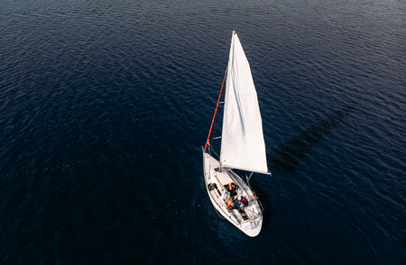 Boat with three passengers orange life jackets develops white sail in wind among blue waters and casts shadow. Top view aerial drone Stock Photo
