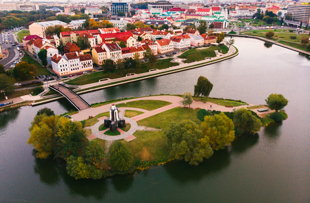 Small island Park, in middle river, planted trees, alleys Orthodox monument center. Stone bridge leading to historic city quarter with red roofs. Minsk, Republic of Belarus. Top view aerial drone