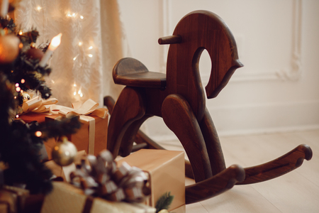 Wooden horse toy under Christmas tree surrounded by gifts for children.