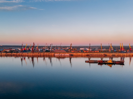 Port river cranes loading ships on barges delivery, sunset. Aerial drone