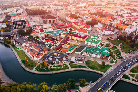 Undulating bend river, bridge, many cars, through which leads to historic district city unusual buildings, small houses, colored roofs . Minsk, Republic of Belarus. Top view aerial drone