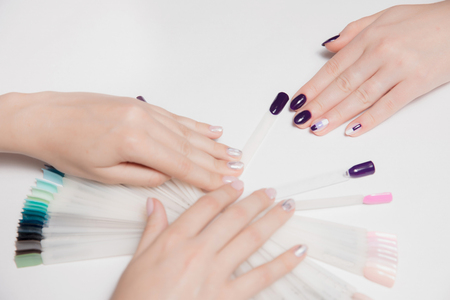 Velvety well-groomed female hands with light by sudovym nail Polish craftsmen and purple manicure client. Selecting new color from palette