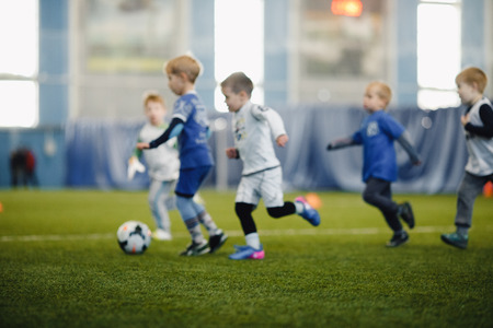 Blurred background of soccer football kids playing and kicking ball. Foto de archivo - 115613154
