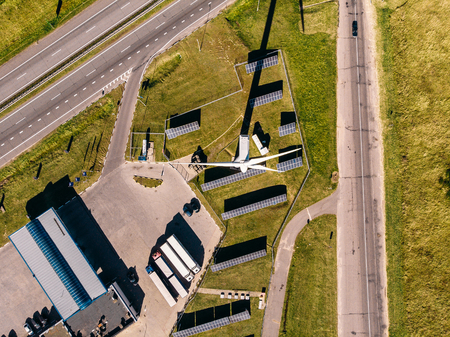 Top VIEW of three roads leading to station which generates electricity using solar panels and wind stations on Sunny summer day