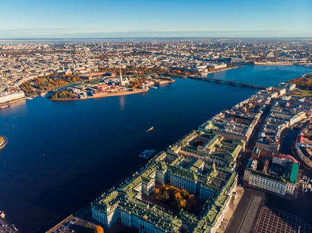 Top view aerial drone on buildings Palace embankment, wide Neva river with boats, bridge. Hare island and Peter and Paul fortress