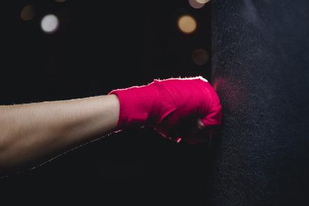 Gros plan de la main dans le poing rose un bandage isolant protecteur frappe un sac de boxe sur fond noir. Concept Boxe