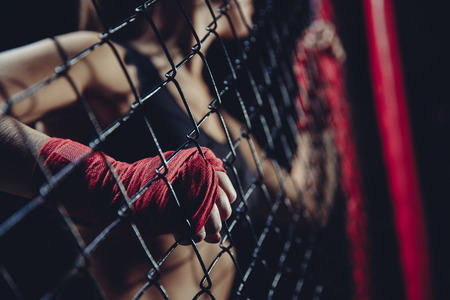 Focus on fist girl athlete MMA in red protective bandage for Boxing and fighting without rules, firmly holding octagon grid