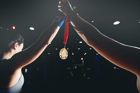 Girl champion blue protective bandages for MMA holds up her hand with gold medal in spotlight Фото со стока