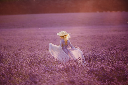 Young woman runs in dress purple lavender field at sunset. France, Provence. Imagens