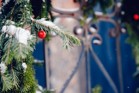 Christmas wreath decorated with red balls hanging on a wrought gate outside the room.