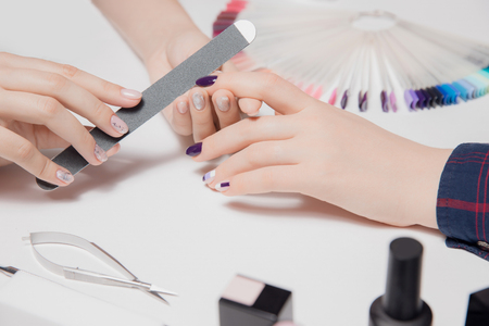 Beautiful well-groomed womans velvet hands. Manicure process. Glossy coating. Purple, nude nail polish. Tools and color palette in frame