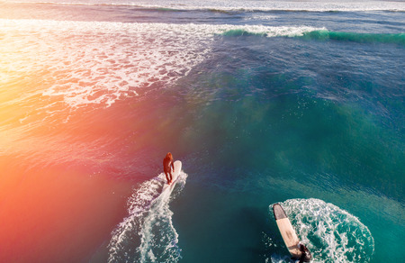 Team of friends in wetsuits surfing on blue water aerial photo Stock Photo