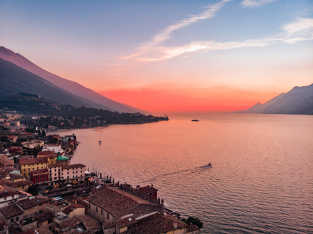 Lake Lago Garda - view of Malcesine village. Old castle on rock Italy. Aerial photo sunset