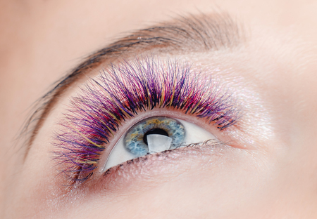 Eyelash extension procedure. Beautiful woman with long colored hairs lash in beauty spa salon.