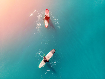 Team of friends in wetsuits surfing on blue water aerial photo