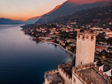 Lake Lago Garda - view of Malcesine village. Old castle on rock Italy. Aerial photo sunset Stock Photo
