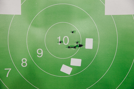 Shooting range gun. Paper target in white and green color for hit.