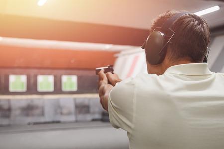 Mężczyzna strzela z pistoletu w słuchawkach chroniących przed hałasem. Pistolet strzelecki. Zdjęcie Seryjne