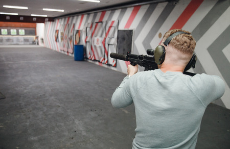 Shooting range gun. Man shoots pistol in noise protection headphones.