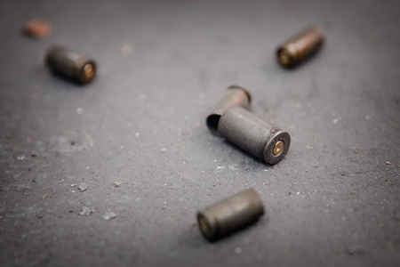 Bullet shell on gray concrete background. Shooting range.