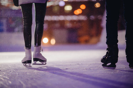 Man and woman skate night on winter skating rink, in background bokeh illumination. Concept training caring love.