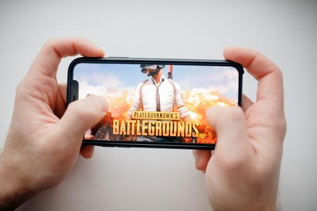 Moscú, Rusia - 1 de enero de 2019: Hombre que sostiene el teléfono inteligente con Player Unknown Battleground PUBG juegos de disparos en línea. Editorial