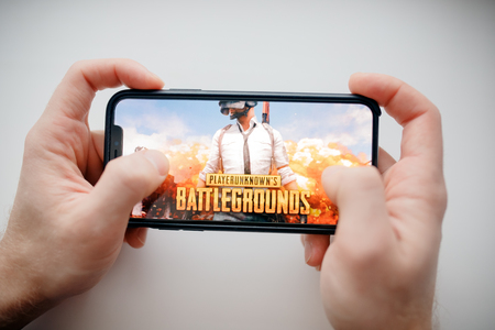 Moscow, Russia - January 1, 2019 : Man holding smartphone with Player Unknown Battleground PUBG online shooting gaming.
