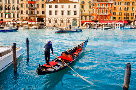 Gondolier carries tourists on gondola Grand Canal of Venice, Italy. Stock Photo