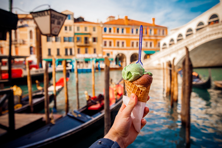 Hand man holds an Italian ice cream on background of Grand Canal and Handol in Venice, Italy. Concept tourism. Stock Photo