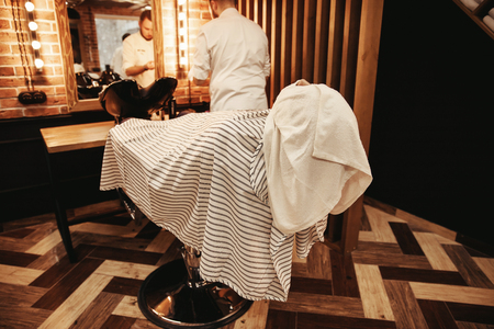 Barber shop, loft interior design, client man in hairdresser chair with towel over his face and striped dressing gown Stock Photo